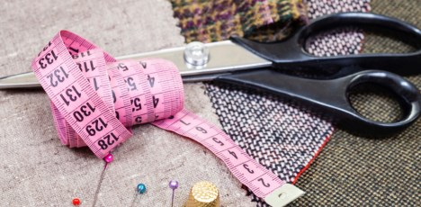 pink measure tape, pins, thimble, shears on cloth